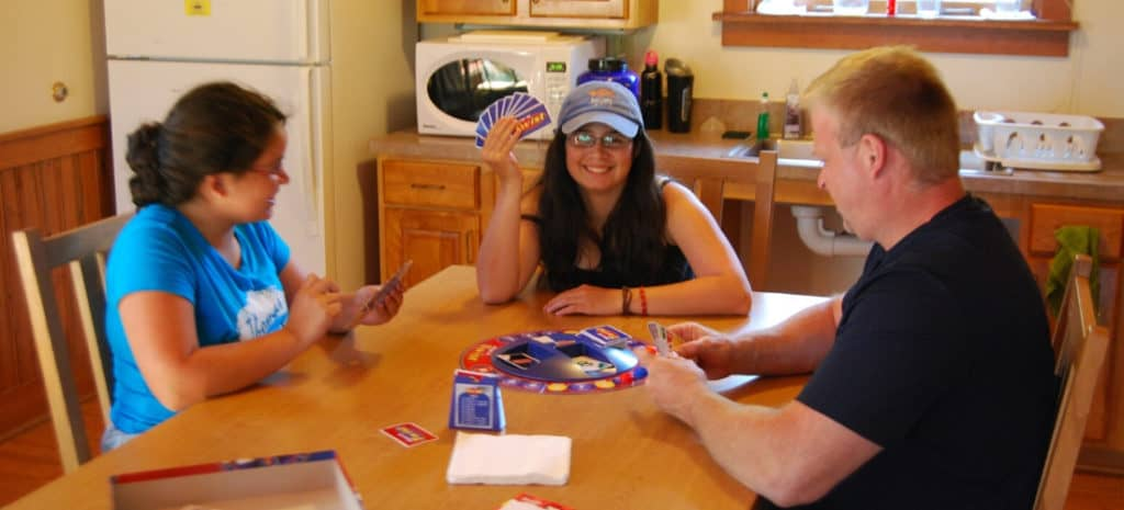 Family playing a board game around the kitchen table