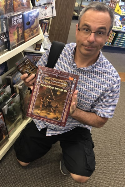 Rich holding a D&D (Dungeons and Dragons) handbook in a hobby shop. Handbooks are helpful when you first start playing.