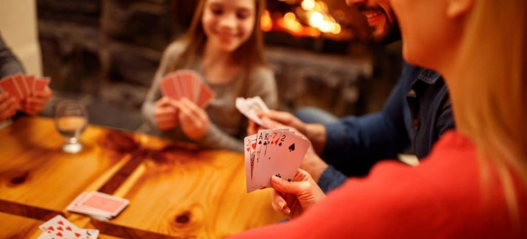 Family playing a game of cards around the table