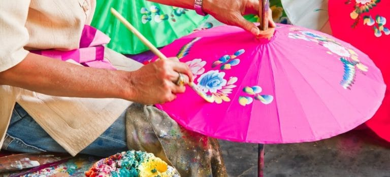 Woman painting on the fabric of an umbrella