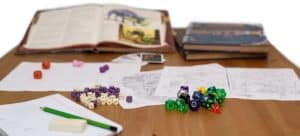D&D game pieces, books, and papers spread out on table.