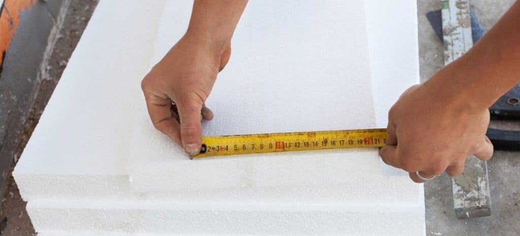 Tape measure being used to measure foam block.
