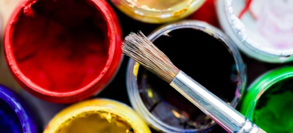 Small paint brush resting on several brightly colored jars of paint.