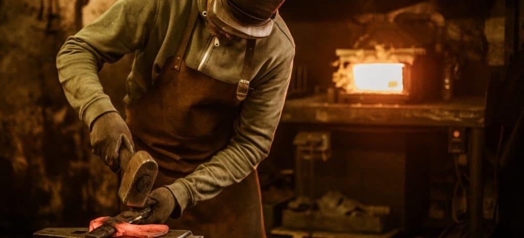 Blacksmith working on an axe with his forge in the background.