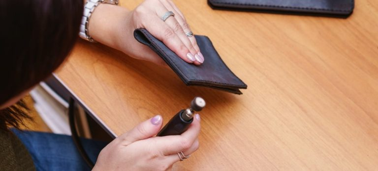 Woman burnishing the edge of a black wallet.
