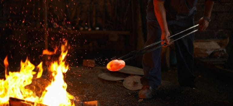 Blacksmith removing red-hot item from the fire.