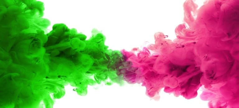 Green and pink spray paint being sprayed into water.
