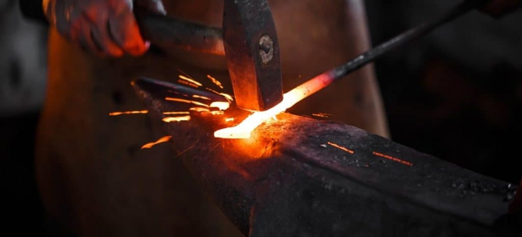 A blacksmith hammer molding a red-hot item with sparks flying.