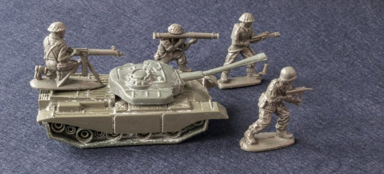 Plastic army men and a tank on gray carpet.