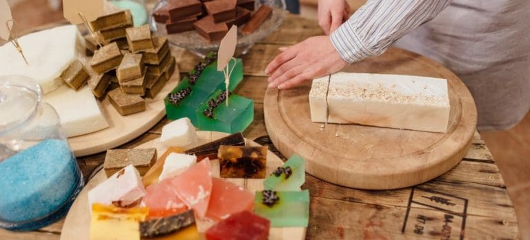 Woman slicing a homemade soap loaf with a knife.