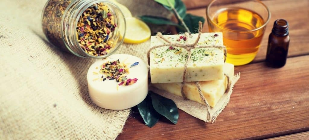 Three bars of homemade soap surrounded by a jar of herbs and fragrance oils.