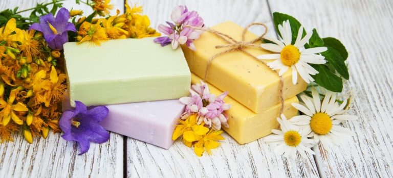 Homemade pastel soaps surrounded by flowers.