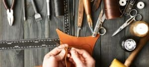 Person sewing a piece of leather with an assortment of tools on the table.