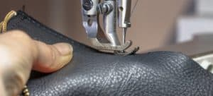 Piece of black leather being stitched on a sewing machine.