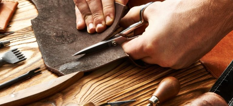 A piece of dark brown leather being cut with scissors.