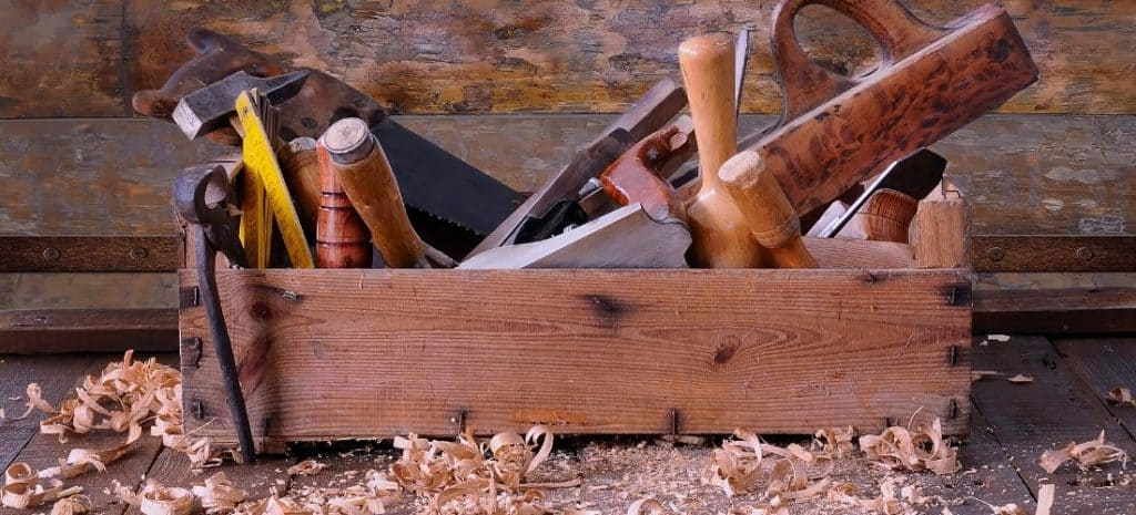 Old wooden toolbox filled with hand tools.