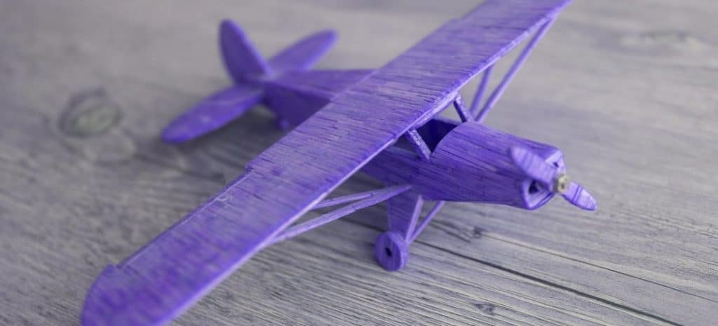 Assembled wooden model airplane painted purple.