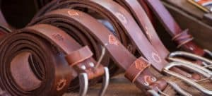 Five rolled-up leather belts in a row.
