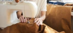 A sewing machine being used to stitch a large piece of leather.