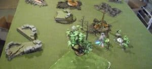 Wargame set up on green felted table with various stone scenery and trees.