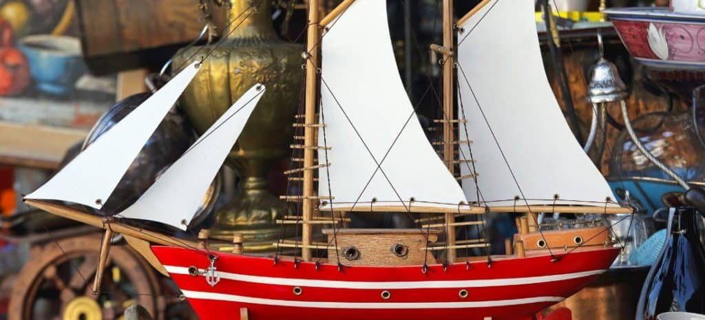 Completed wooden model of ship with red and white striped hull.