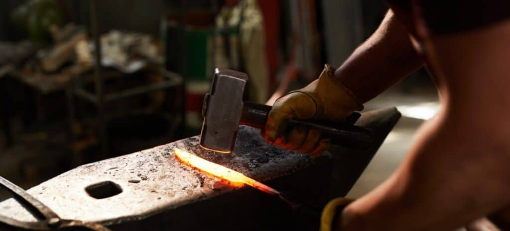 Blacksmith using a hammer and anvil to shape a piece of red-hot metal.
