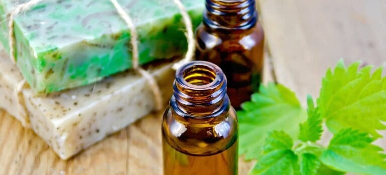 Two open bottles of essential oil, two homemade soaps, and peppermint leaves.