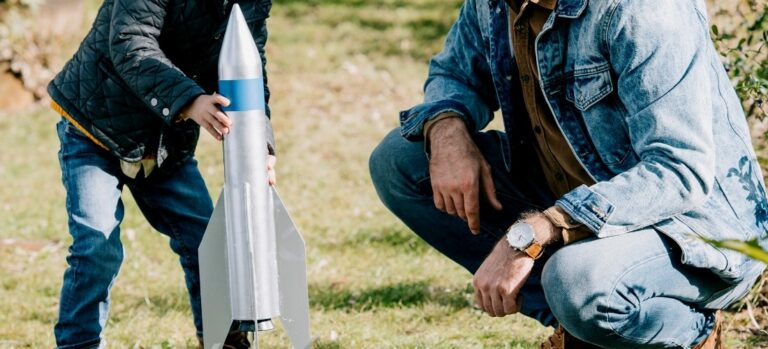 Little boy and man setting up model rocket to launch.