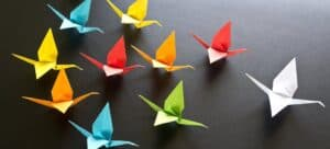 A display of brightly colored origami cranes on a dark table.