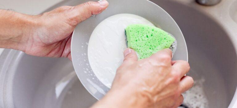 Man washing a dish with a green sponge.