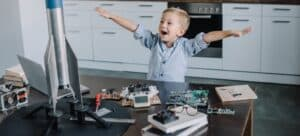 Little boy displaying his silver model rocket on kitchen table.