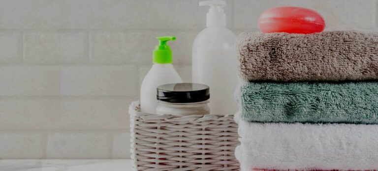 Two pump bottles and a jar of homemade laundry products sitting in a basket beside a stack of folded towels.