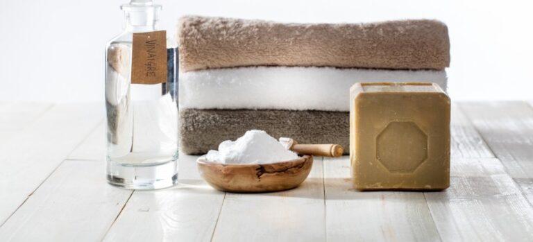 Three folded towels, a jar of vinegar, a bowl of washing soda, and a bar of soap.