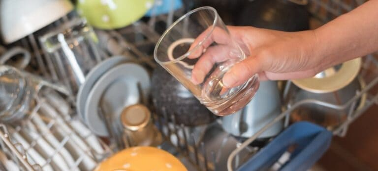 A clean glass being removed from the dishwasher.