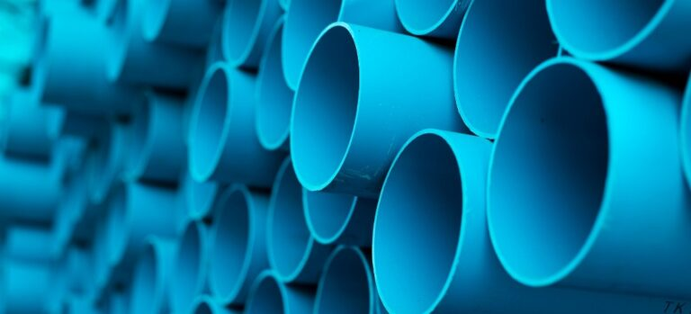 Large stack of blue PVC pipes.