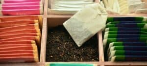 A wooden box of different colored tea bags.