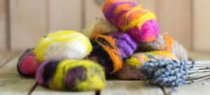 Several bars of colorfully felted soaps.