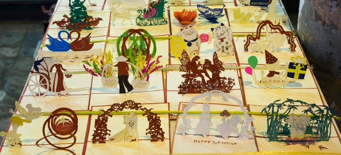 An assortment of kirigami creations including a sleigh and fairies.