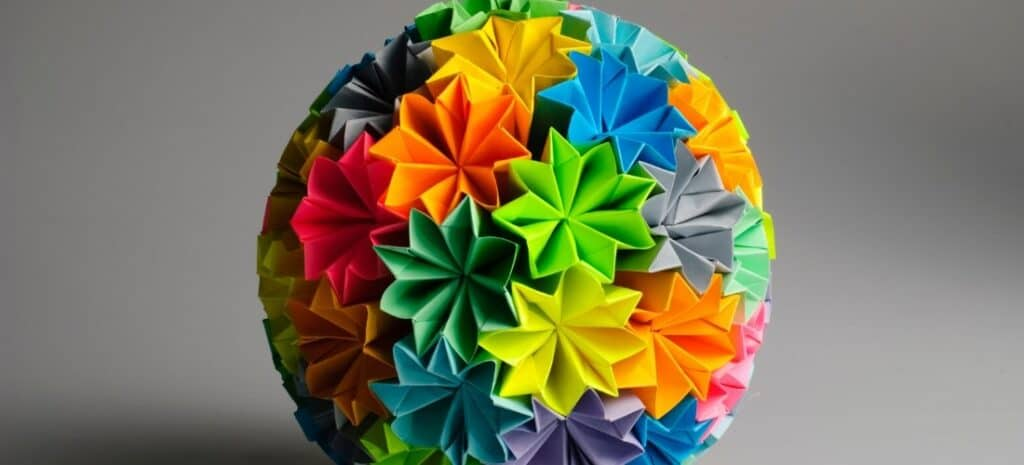 Brightly colored modular origami sphere made up of individual flower units.