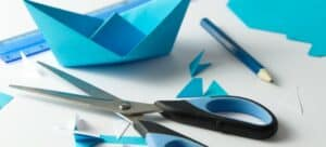 A pair of scissors and a pencil lying beside a blue origami boat.