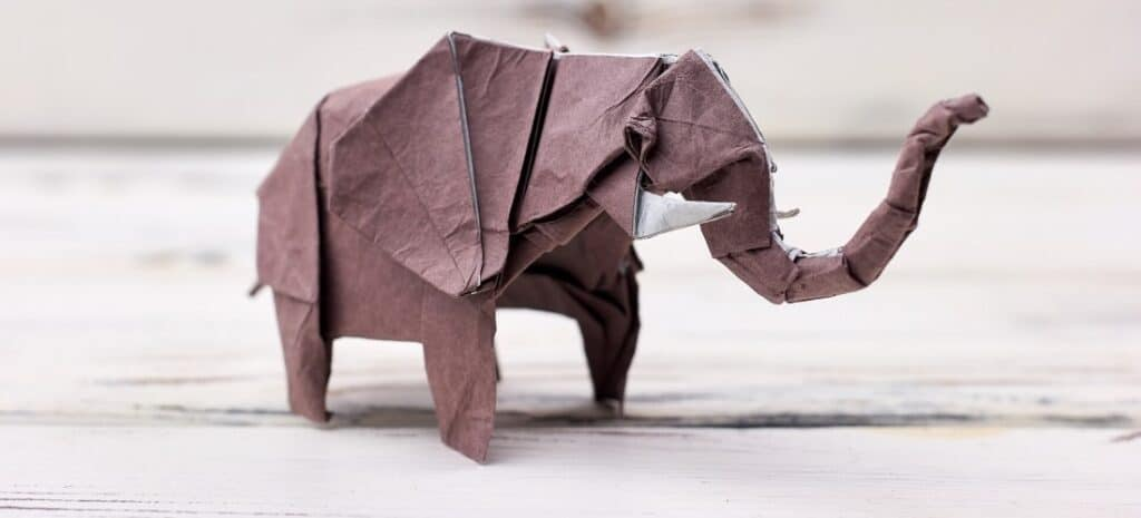 Gray origami elephant created by wet folding.