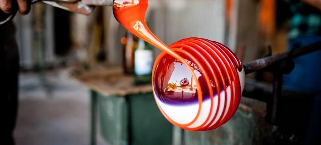 A pontil being used to add colorful stripes to hand-blown glass.