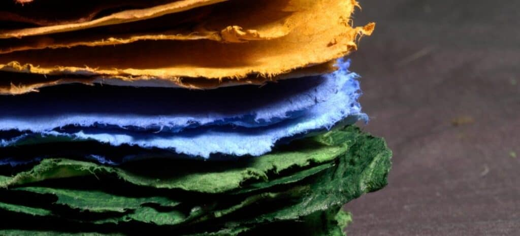 Stack of handmade paper in green, blue, and orange.