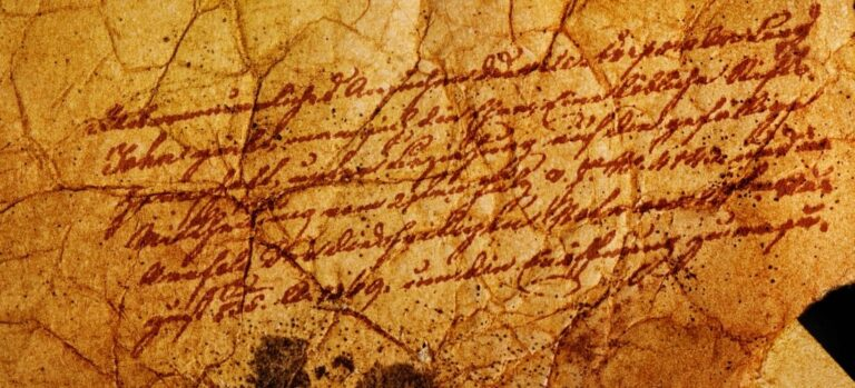 A crinkled, aged piece of paper with indecipherable words.