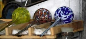 Three long-stemmed blown-glass pieces in green, red, and blue.