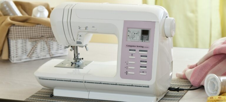 A white and pink sewing machine on a table.