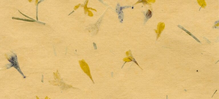 A sheet of handmade paper tinted beige and decorated with small flowers.