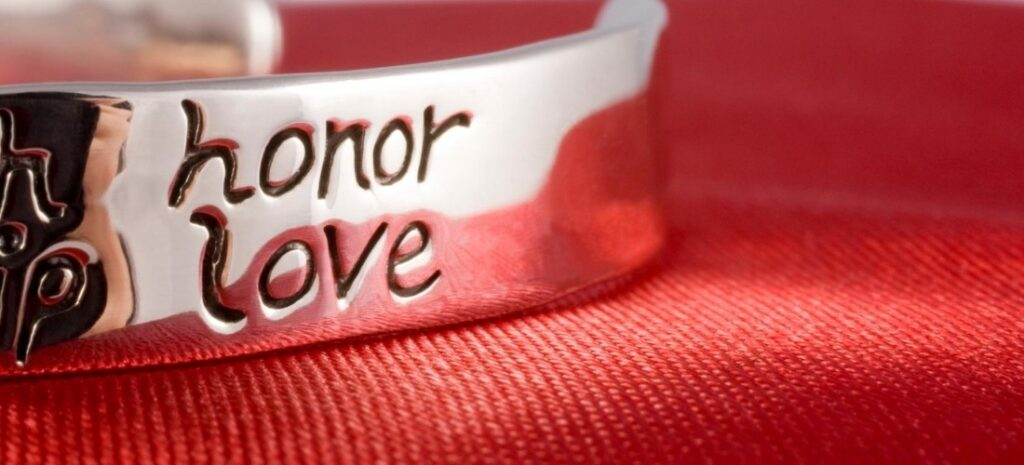 "A silver bracelet with ""honor love"" engraved on the side."