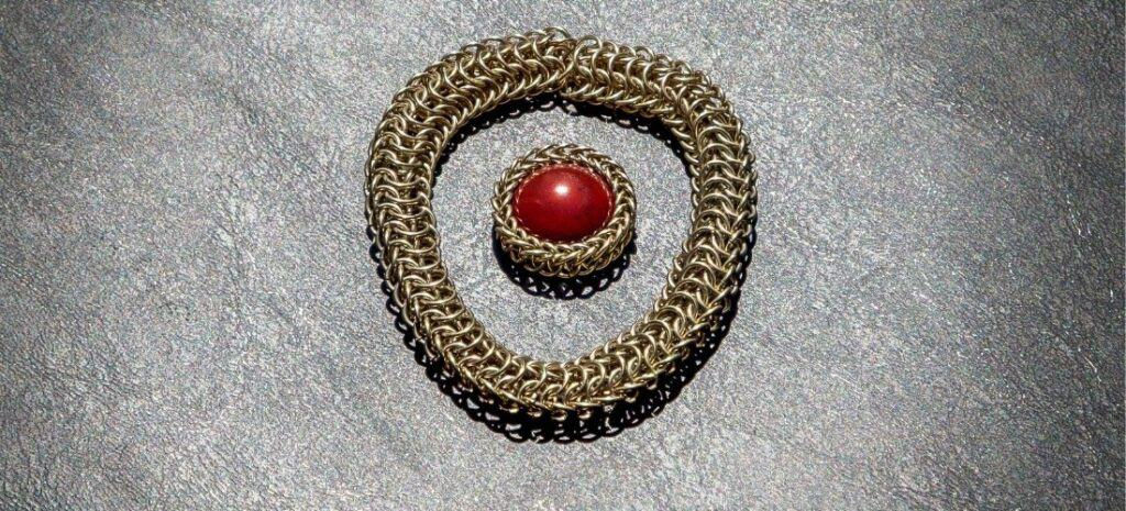 A gold chain mail bracelet and a matching ring.
