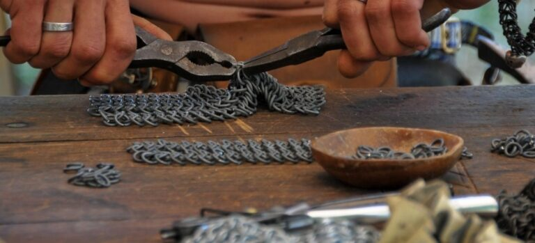 A man using two pliers to make a sheet of chain mail.